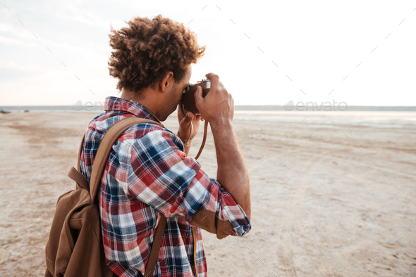 African man with backpack taking pictures on the beach - Stock Photo - Images
