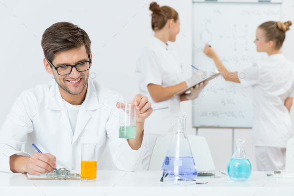 Young scientist writing down his findings - Stock Photo - Images
