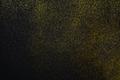 Golden glitter sand texture on black, abstract background.