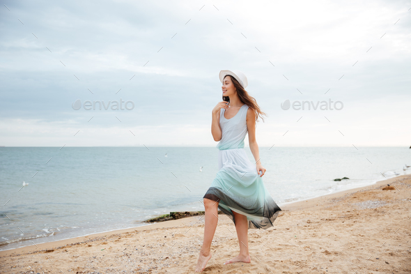 Woman in white hat and dress walking on the beach - Stock Photo - Images