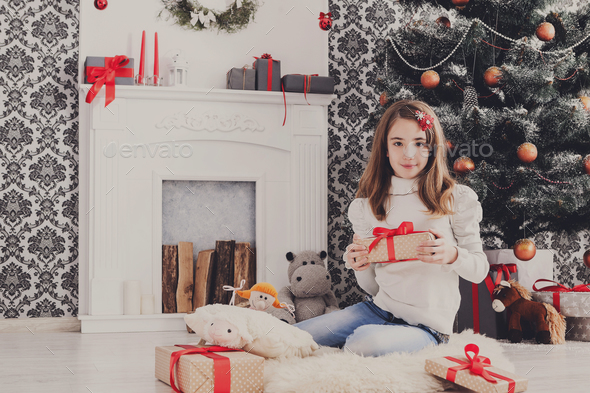Beautiful girl in santa hat unwrapping christmas presents - Stock Photo - Images