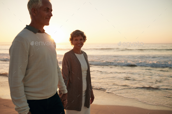 Senior woman with her husband strolling on the beach - Stock Photo - Images