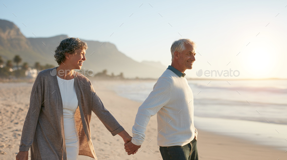Senior couple walking together on the beach - Stock Photo - Images