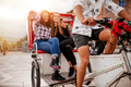 Young women sitting on tricycle and looking at mobile phone