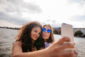 Teenage girls taking selfie with smart phone by the lake