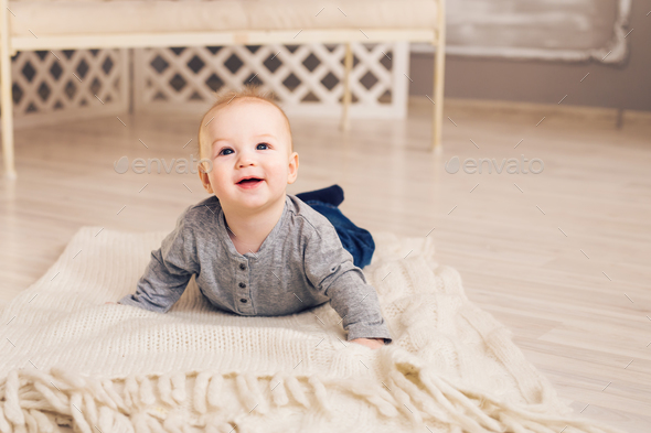 Adorable baby boy in sunny bedroom - Stock Photo - Images
