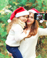 Christmas smiling mother and child taking picture self portrait