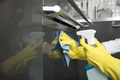 Closeup of female hands in gloves cleaning oven, holding spray - PhotoDune Item for Sale