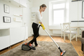 Woman in casual wear vacuum cleaning the carpet - PhotoDune Item for Sale