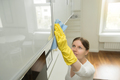 Young attractive woman cleaning an upper surface of kitchen clos - PhotoDune Item for Sale