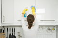 Rear view at young woman cleaning white kitchen wall cabinet - PhotoDune Item for Sale