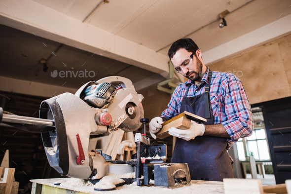 Young craftsman in uniform working at carpentry - Stock Photo - Images