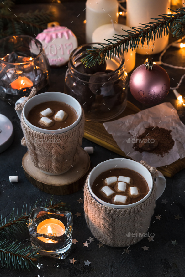 Two cups in knitted mittens of fresh hot cocoa or chocolate - Stock Photo - Images