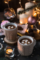 Two cups in knitted mittens of fresh hot cocoa or chocolate