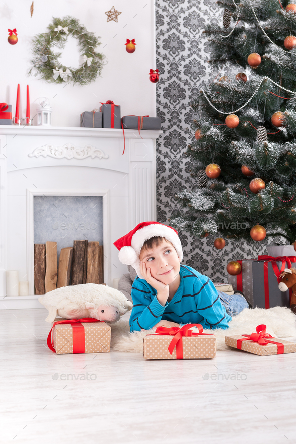 Cute boy in santa hat unwrapping christmas presents - Stock Photo - Images