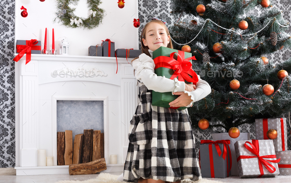 Beautiful child girl and christmas present indoors - Stock Photo - Images