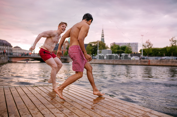Young friends about to jump into the lake - Stock Photo - Images