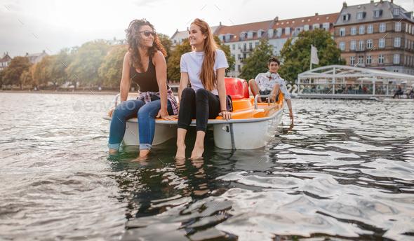Teenage friends enjoying boating in the lake - Stock Photo - Images