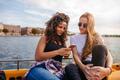 Female friends using smart phone on boat in lake