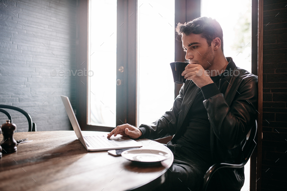 Young man using laptop at cafe - Stock Photo - Images