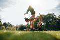 Couple doing acro yoga in park