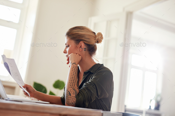 Woman going through contract papers at home office - Stock Photo - Images