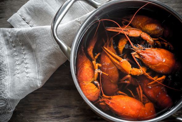 Pot with boiled crayfish on the wooden table - Stock Photo - Images