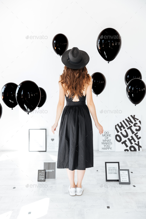 Back view of woman in hat standing over white background - Stock Photo - Images