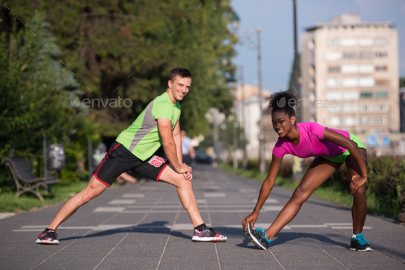 jogging couple warming up and stretching in the city - Stock Photo - Images