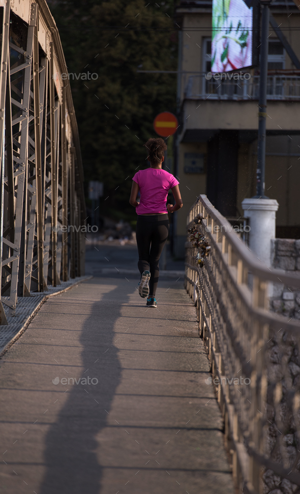 african american woman running across the bridge - Stock Photo - Images