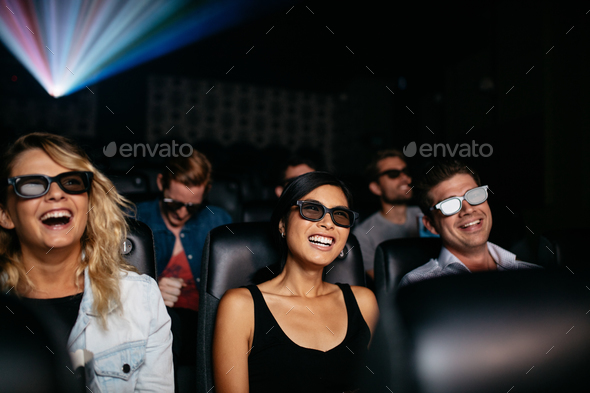 Friends watching 3d movie in theater and laughing - Stock Photo - Images