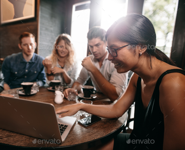 Group of friends in cafe watching something online on laptop - Stock Photo - Images