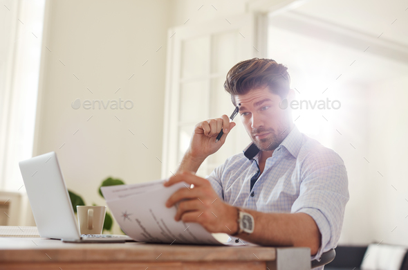 Young man going through paperwork at home office - Stock Photo - Images