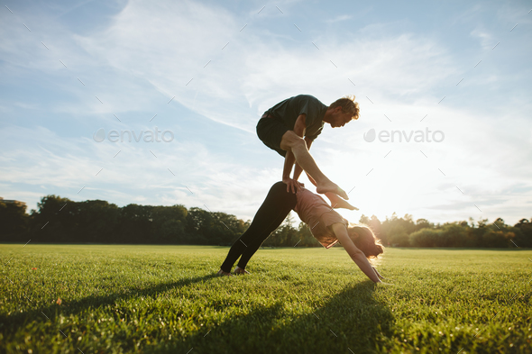 Young couple doing acrobatic yoga on lawn - Stock Photo - Images