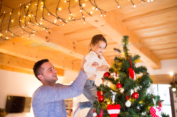 Young father with daugter decorating Christmas tree together. - Stock Photo - Images
