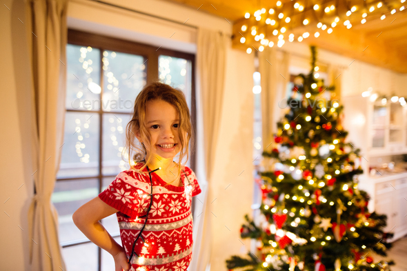Little girl decorating Christmas tree tangled in chain lights. - Stock Photo - Images