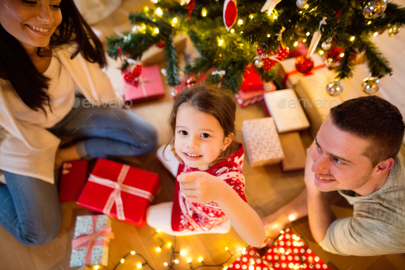 Young family with daugter at Christmas tree at home. - Stock Photo - Images