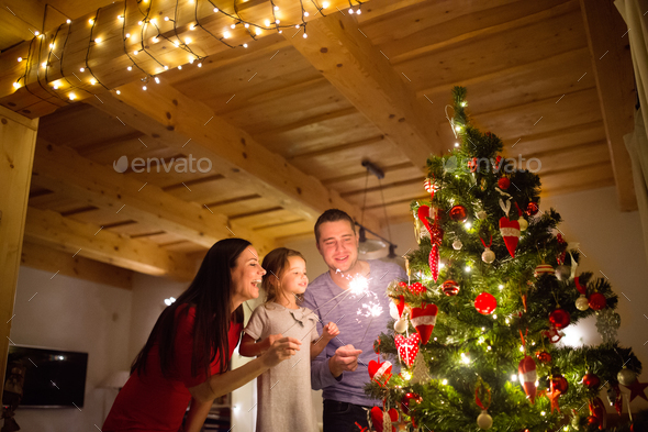 Young family with sparklers at Christmas tree at home. - Stock Photo - Images