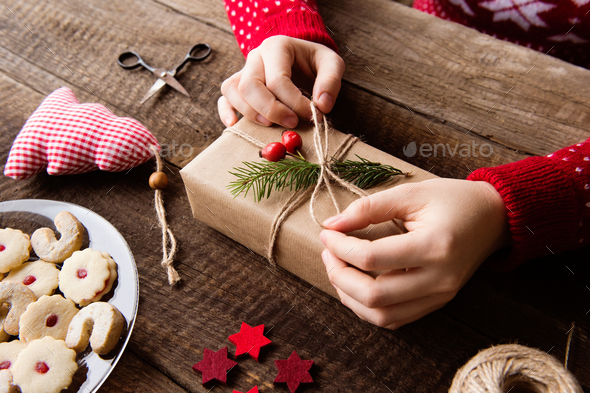 Unrecognizable woman wrapping and decorating Christmas present - Stock Photo - Images
