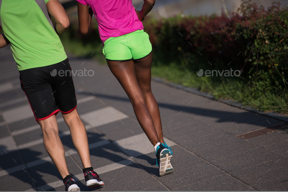 young smiling multiethnic couple jogging in the city - Stock Photo - Images