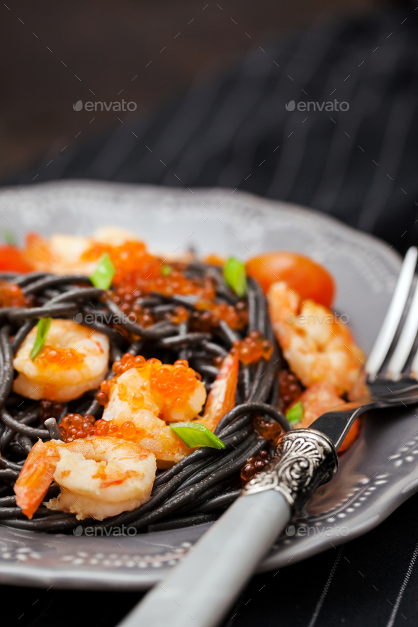 Black spaghetti with shrimps and red caviar - Stock Photo - Images