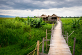Traditional Asian local farm houses and wooden bridge, Inle lake