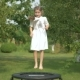 The Cute Girl Jumping on Trampoline in the Garden - VideoHive Item for Sale