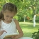 The Girl Playing on the Tablet in the Garden - VideoHive Item for Sale