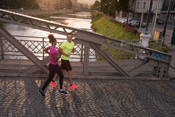 young multiethnic couple jogging in the city - Stock Photo - Images