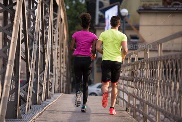 multiethnic couple jogging in the city - Stock Photo - Images