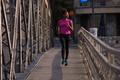 african american woman running across the bridge
