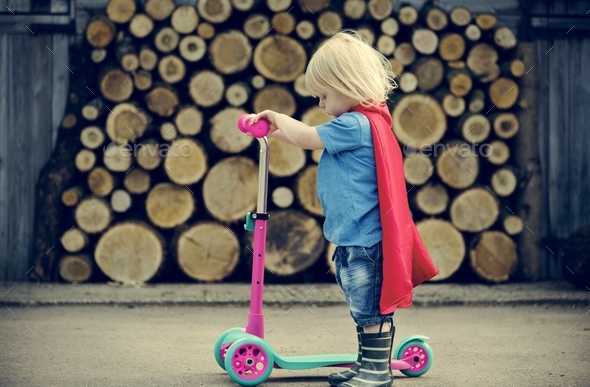 Superhero Baby Boy Using Scooter Adorable Concept - Stock Photo - Images