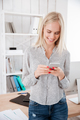 Woman texting messae on mobile phone while standing at office - PhotoDune Item for Sale