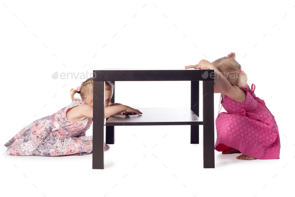 two little girls hiding behind table - Stock Photo - Images